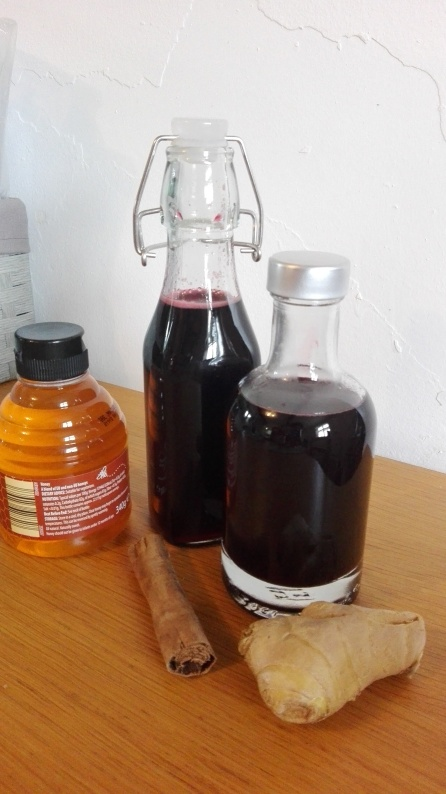 bottles of elderberry syrup with honey cinnamon and ginger
