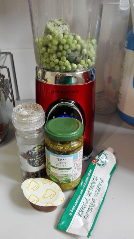 blender with spinach and peas, pepper, pesto, stock and garlic paste on a kitchen worktop