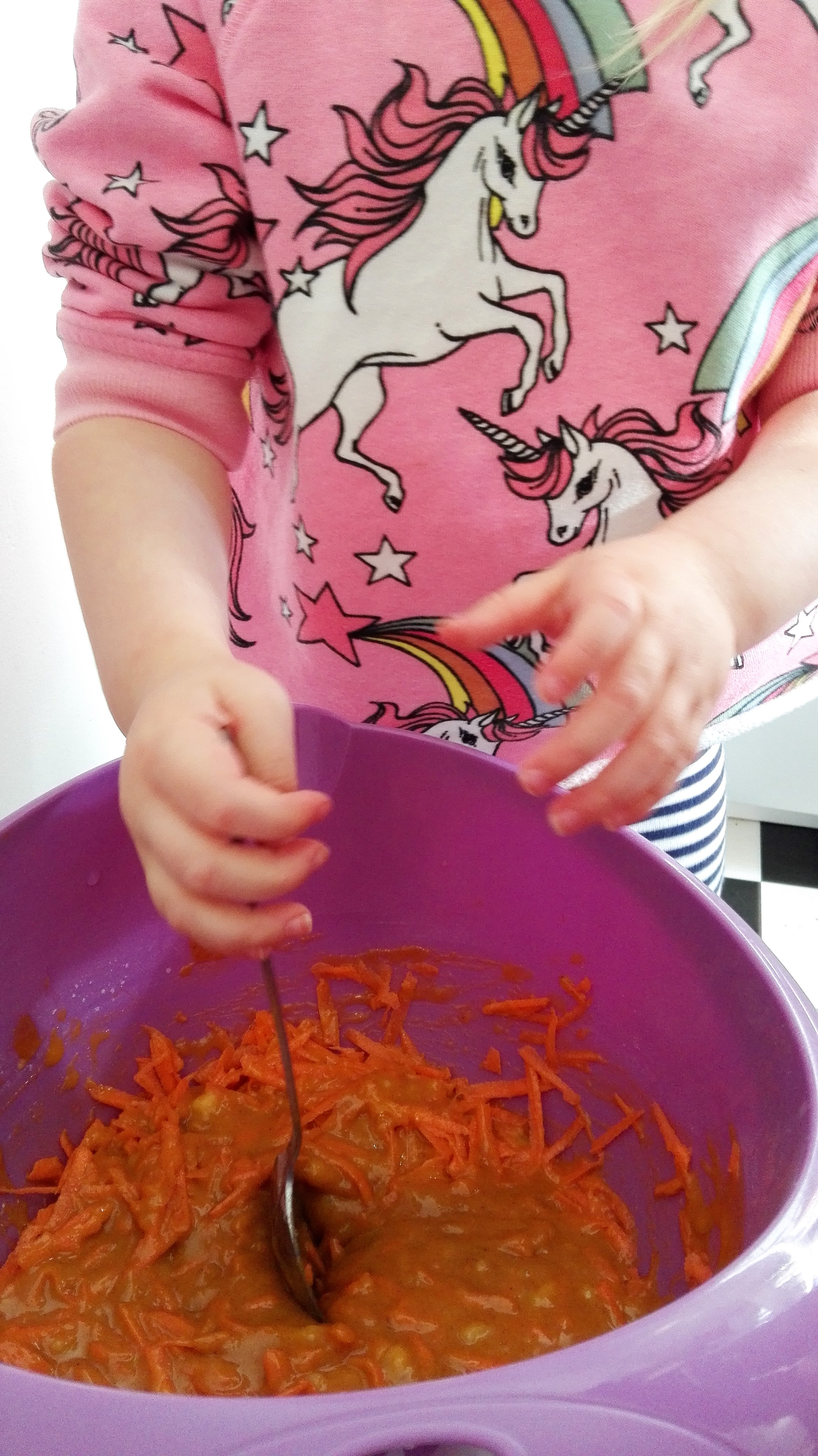 purple mixing bowl with ingredients in being mixed by child