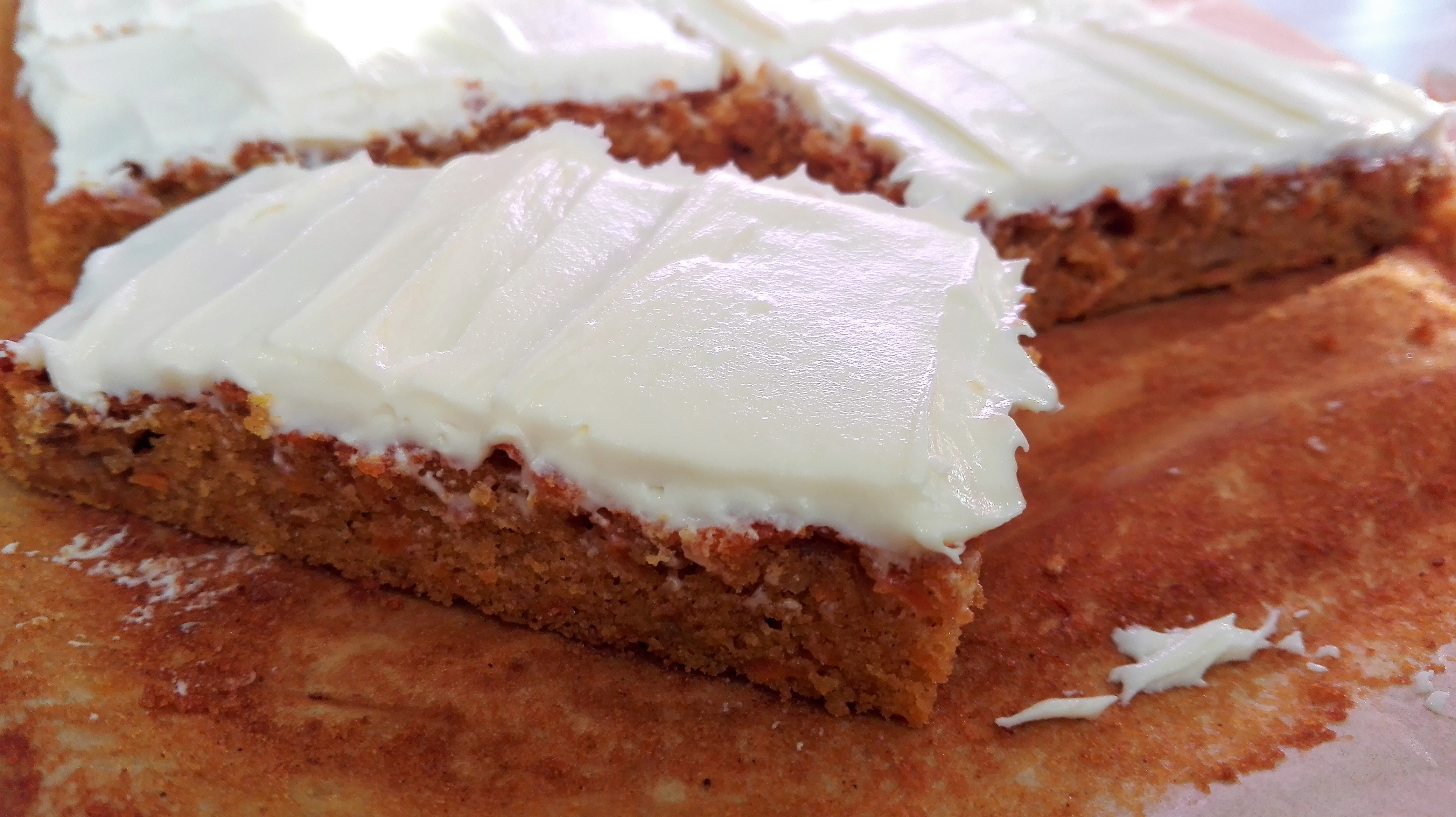 slice of gluten free carrot cake traybake with cream cheese frosting