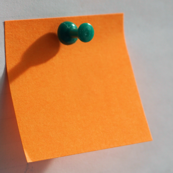 blank orange post it note with a green pin in it