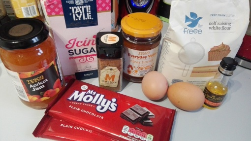 gluten free lebkuchen ingredients - apricot jam, icing sugar, mixed spice, honey, 2 eggs, gluten free flour and 2 bars of dark chocolate on a kitchen worktop