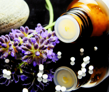 homeopathic pillules remedy in bottle with lavender flowers on a table