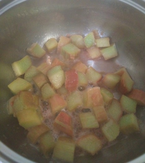 Chopped rhubarb simmering in a pan over a medium heat to make rhubarb & ginger chia jam