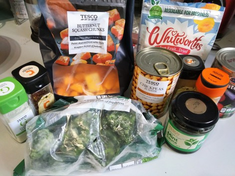 vegan moroccan tagine ingredients - garlic, crushed chillies, butternut squash chunks, tinned chickpeas, dried apricots, raisins, frozen spinach, cumin, turmeric, mint sauce and tinned ratatouille