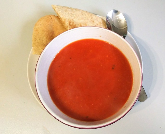 vegan tomato and ginger soup in a bowl on a plate with a spoon and a pitta bread