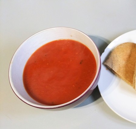 Bowl of tomato, orange and ginger soup on a kitchen counter. Easy vegan dinner recipes
