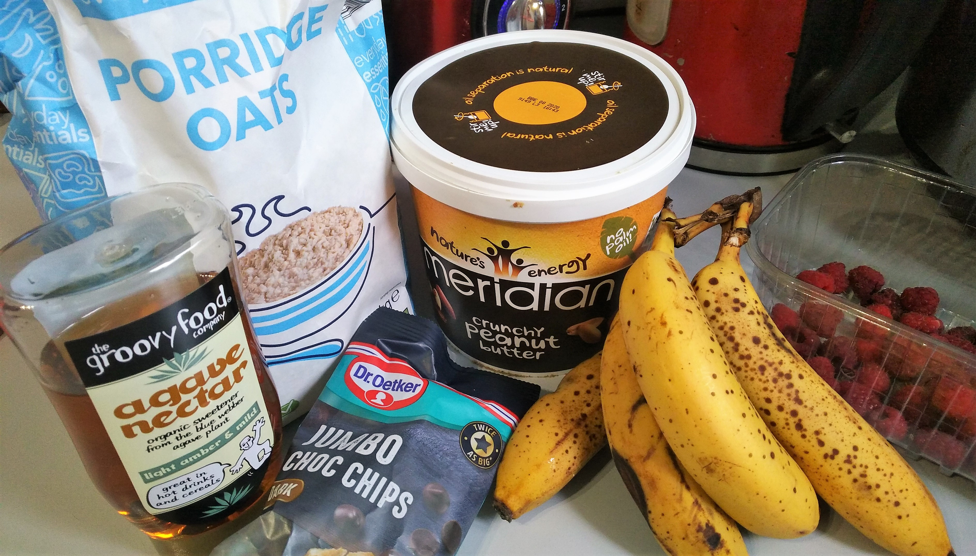easy fruity breakfast bars ingredients - agave nectar, oats, crunchy peanut butter, choc chips, ripe bananas, fresh raspberries