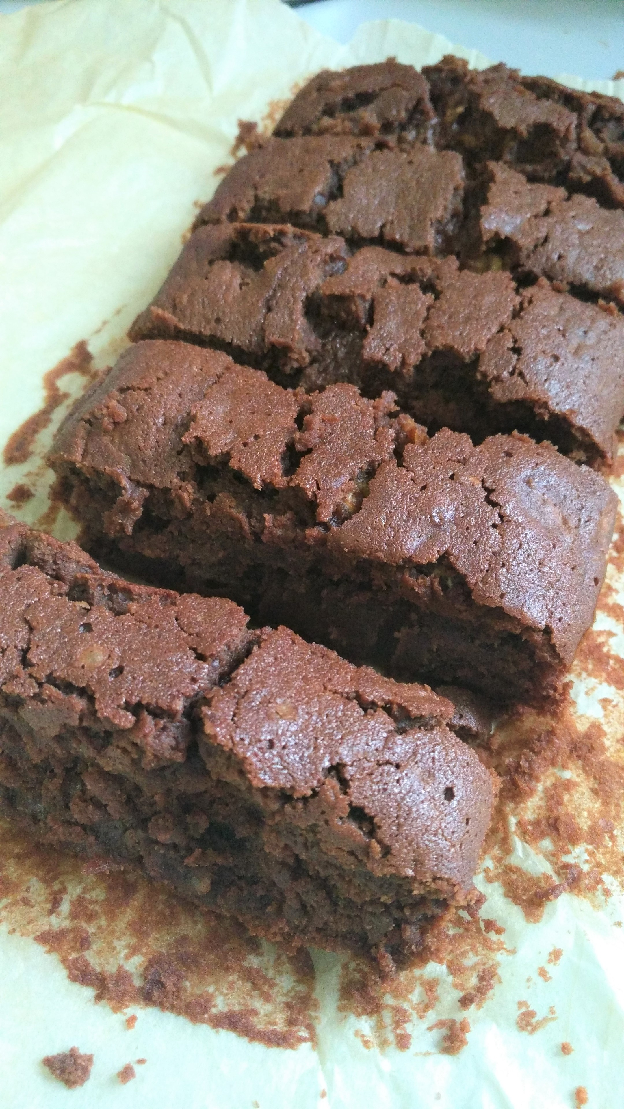 courgette zucchini chocolate brownies fresh out of the oven and sliced on baking paper - a vegan gluten free recipe by Kirstie Anne Wellbeing