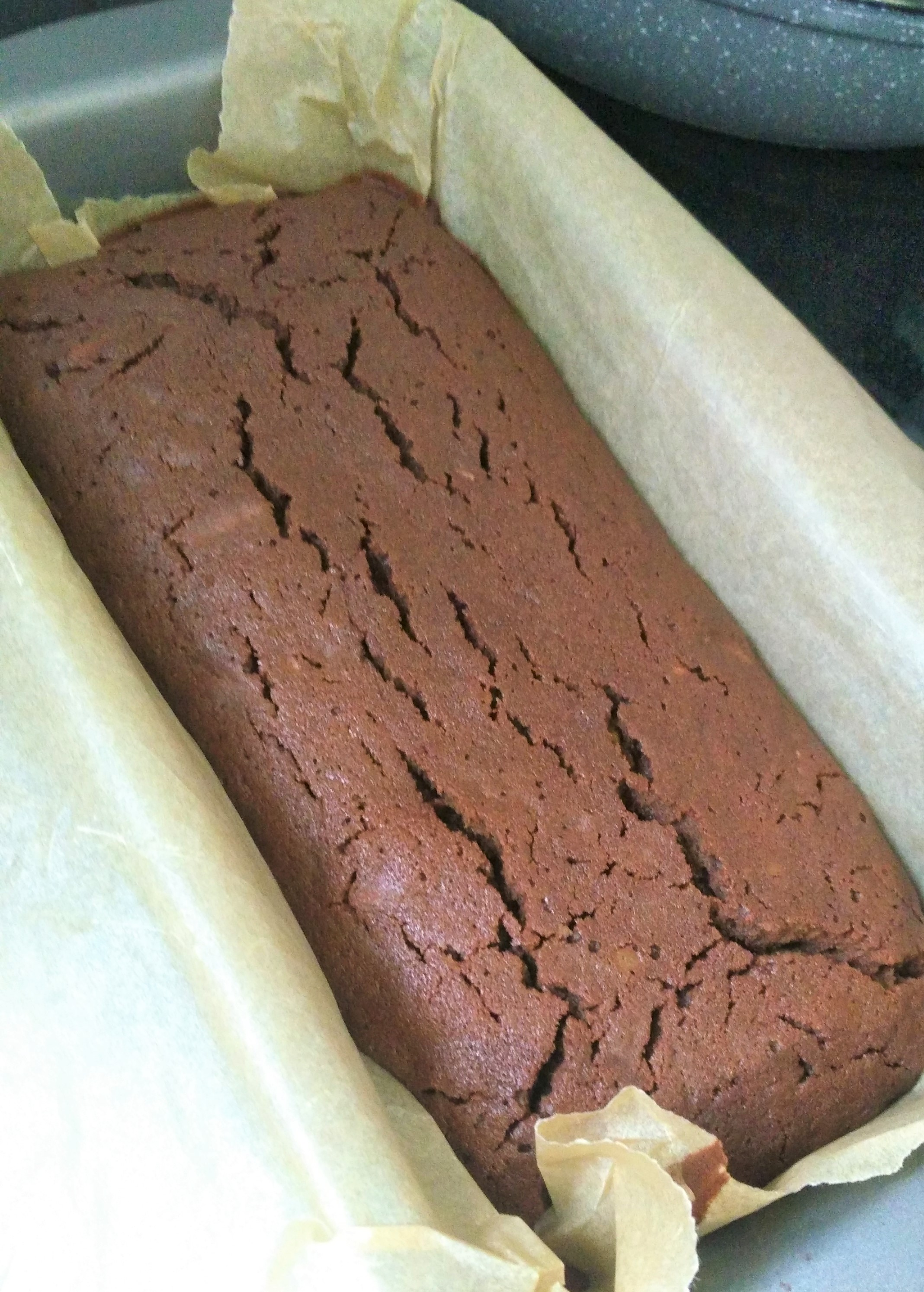 vegan courgette chocolate brownies in a loaf tin with baking paper fresh out of the oven showing the cracking on top when done