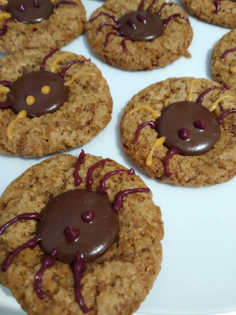 close up of spooky spider halloween almond biscuits decorated with chocolate buttons. gluten free, vegan and sugar free.