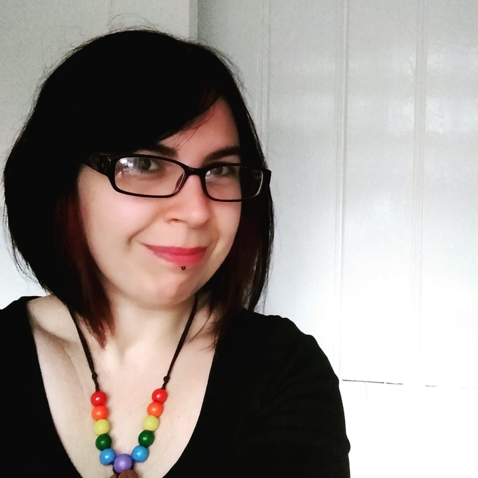 profile photo of Kirstie Anne, I'm wearing glasses and smiling, I have mid-length brown hair and a rainbow  necklace