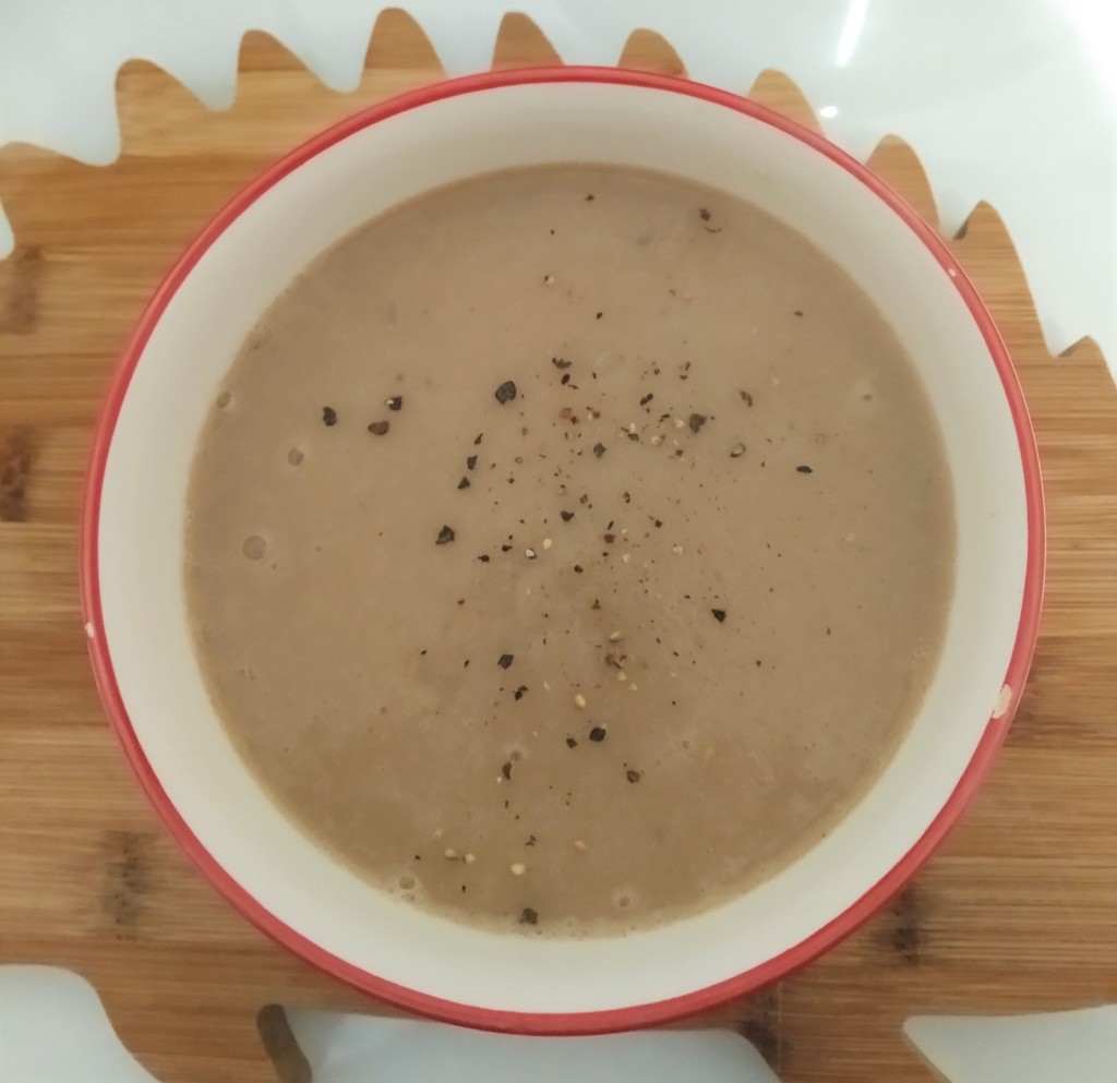 chestnut and parsnip soup in a white bowl on a brown hedgehog shaped chopping board. close up with black pepper