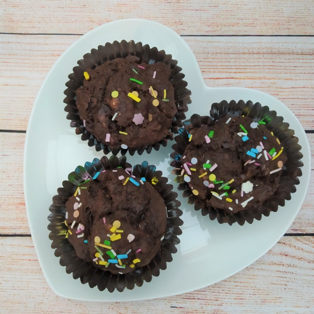 healthy double chocolate banana muffins on a heart shaped plate with rainbow sprinkles on top.