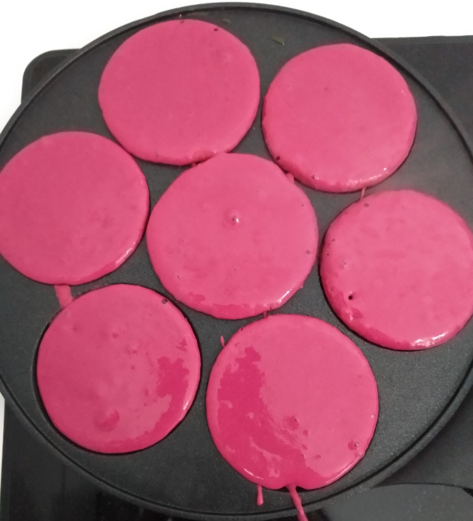 pink buckwheat pancake batter in a multi-hole frying pan for mini pancakes that are perfect for kids