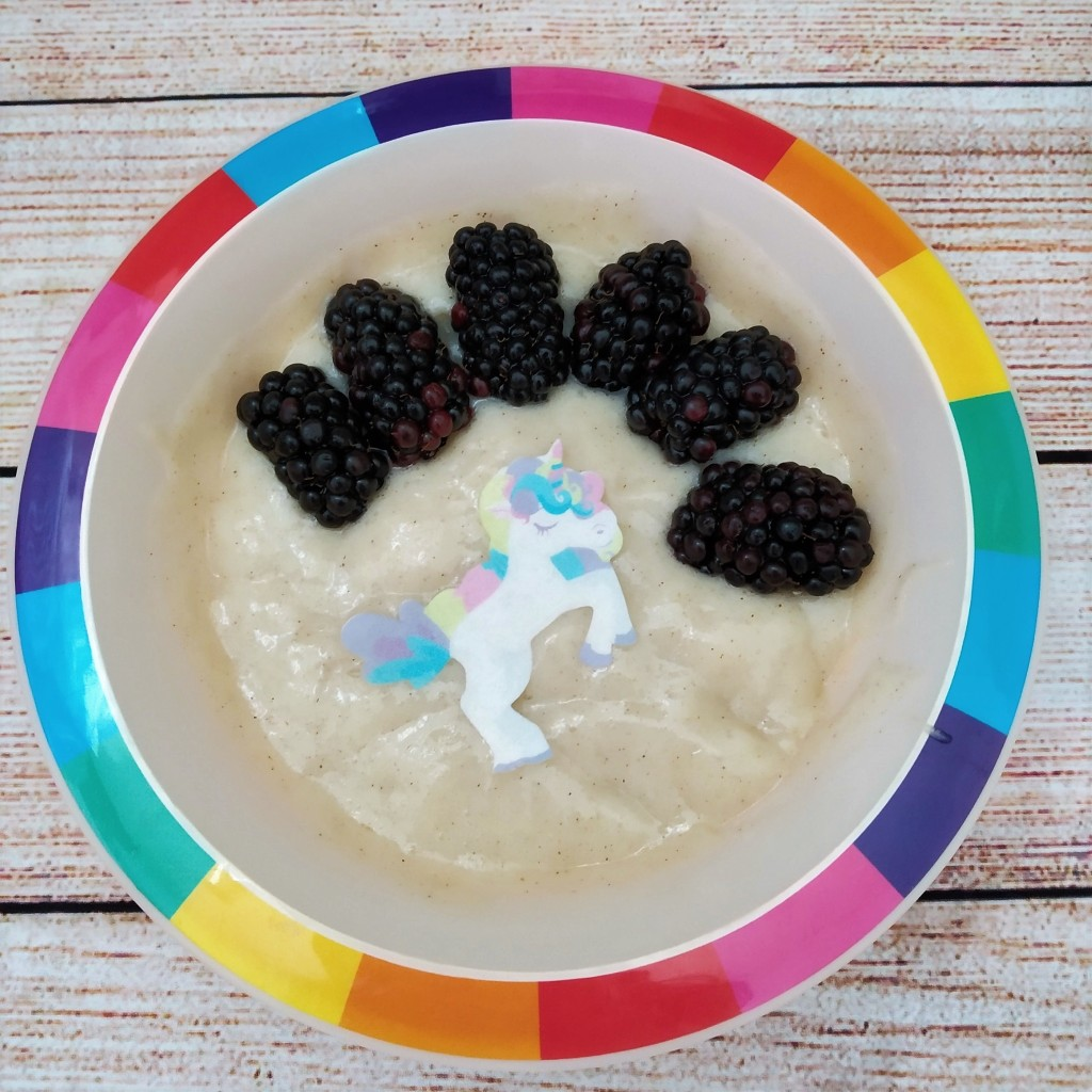 soy free vegan yoghurt with apple and cinnamon in a rainbow bowl, decorated with edible unicorn wafer and blackberries