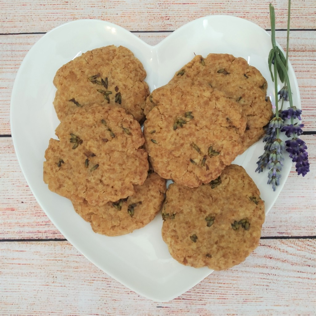 dairy free lavender and ginger biscuits on a white heart shaped plate on a table with fresh sprigs of lavender next to them