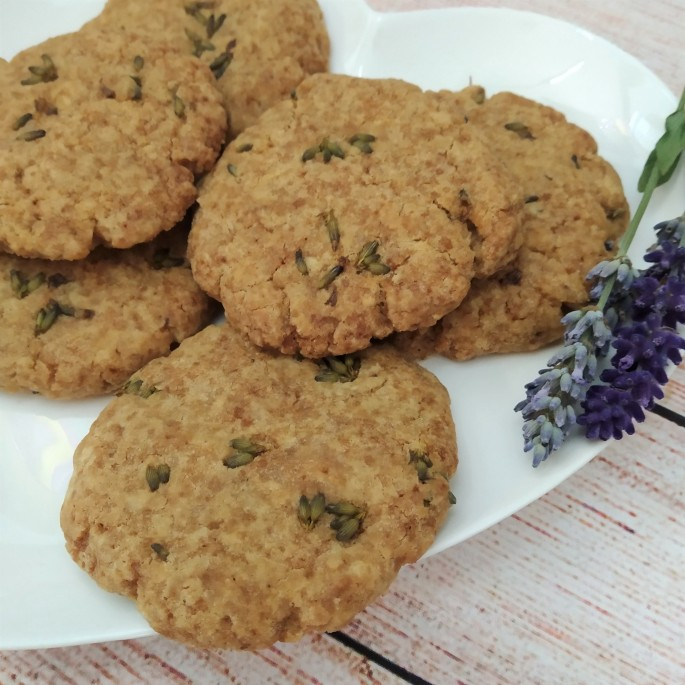 gluten free and vegan lavender and ginger biscuits on a white plate with sprigs of fresh lavender