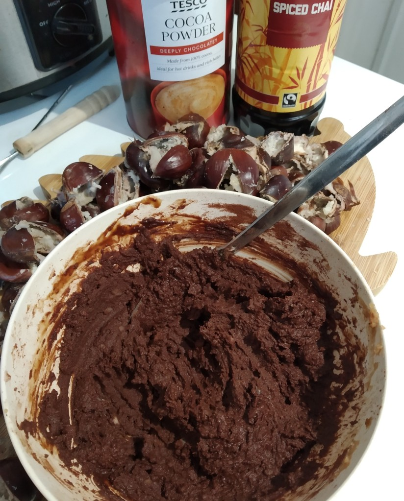 allergy friendly chocolate spread recipe using foraged chestnuts in a bowl on a kitchen worktop. In the background there is a tub of cocoa powder and a bottle of syrup