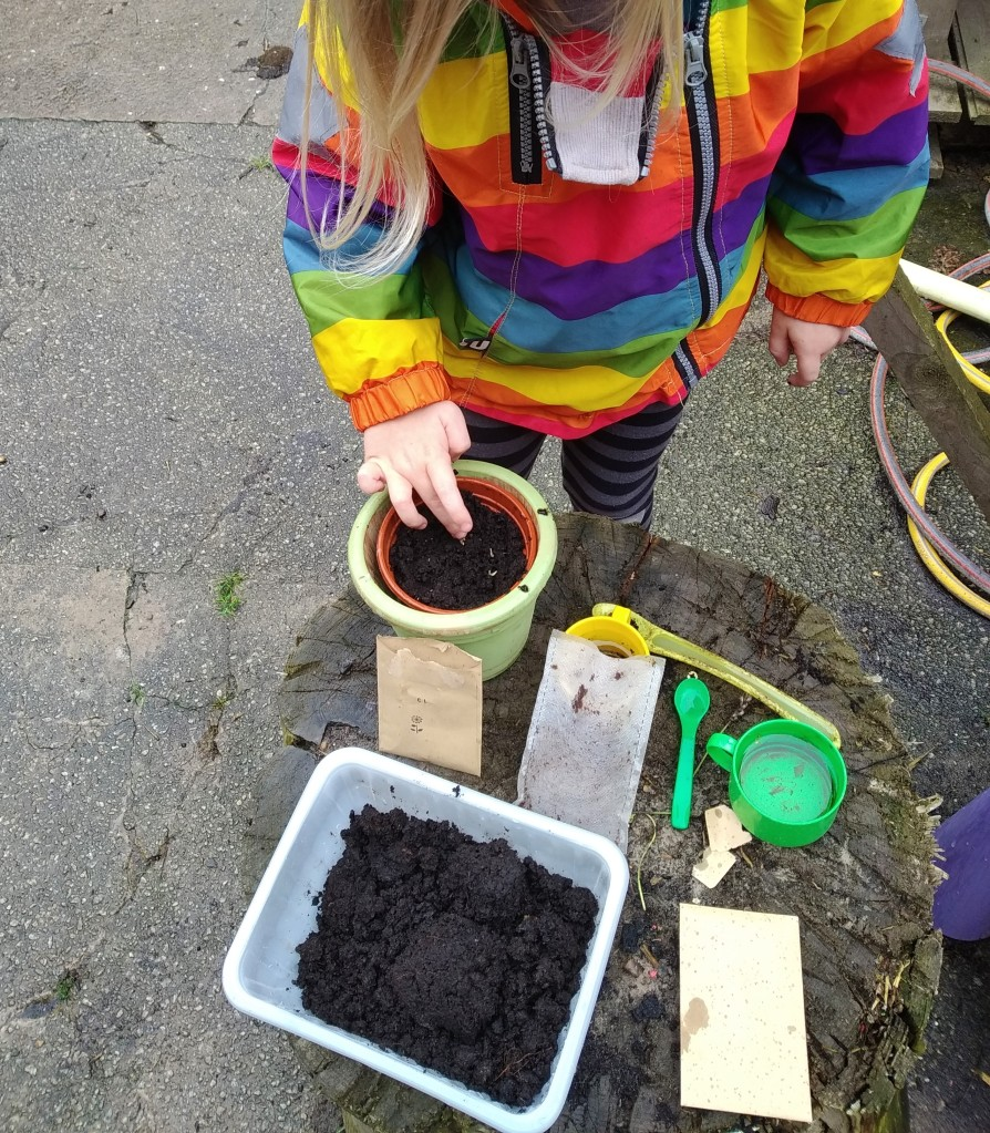 my home educated child in a rainbow coat planting seeds in a pot in the garden