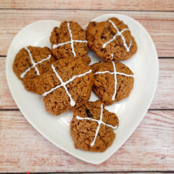 vegan gluten free hot cross bun biscuits cookies on a heart shaped plate on a table